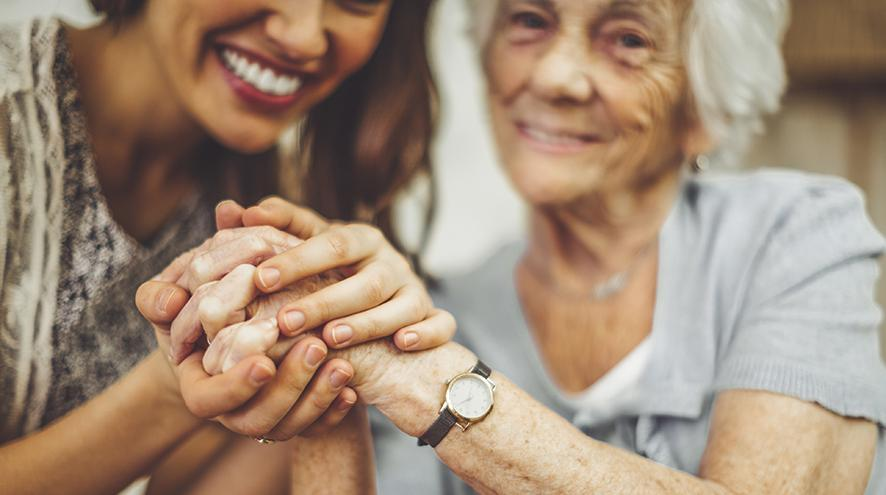 care worker and senior woman holding hands