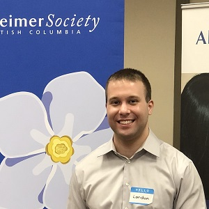 Landon smiling in front of a blue Alzheimer Society of B.C. banner.