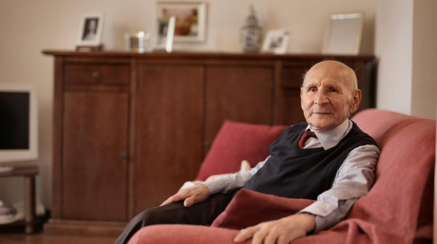 Elderly man sitting in a sofa, looking up at the camera.