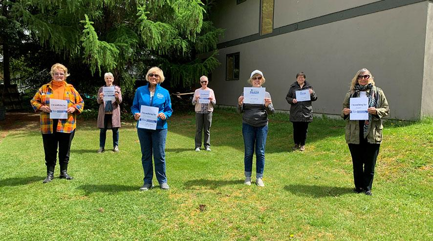Seven volunteers of the IG Wealth Management Walk for Alzheimer's holding signs in support of the event in a social distanced formation