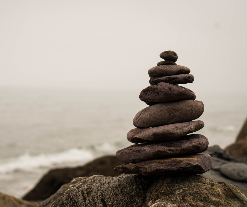 stacked flat rocks in a serene setting of sand and grey sky