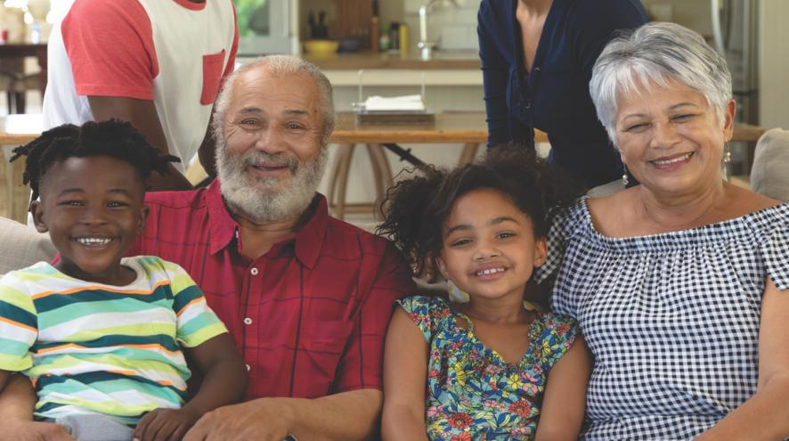 Multi-racial and multi-generational family smiling and sitting on a couch