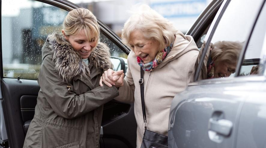 Middle-aged woman helping senior woman out of her car.