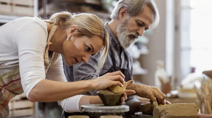 Two people in a pottery class.
