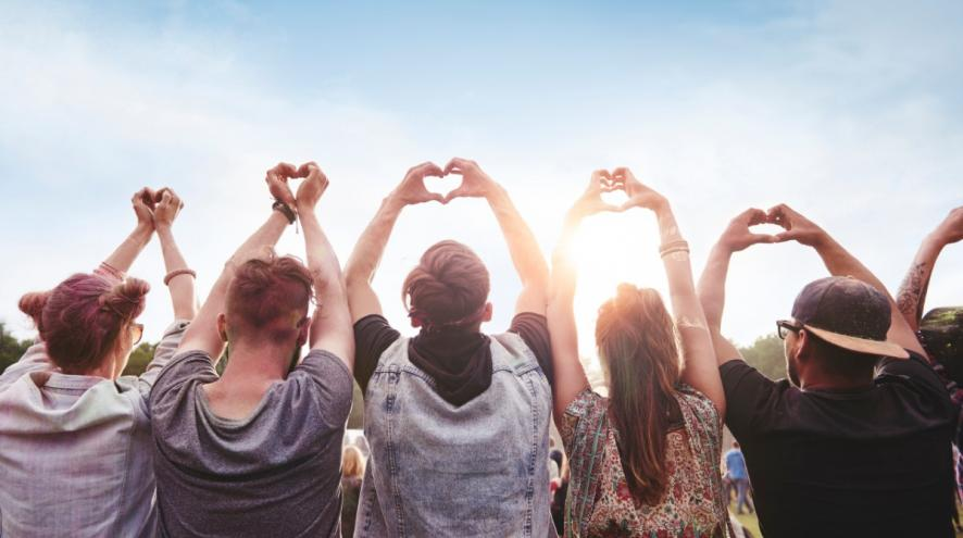 Group of people holding up heart hands.