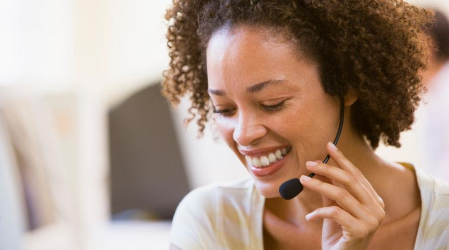 Woman wearing a headset and smiling.