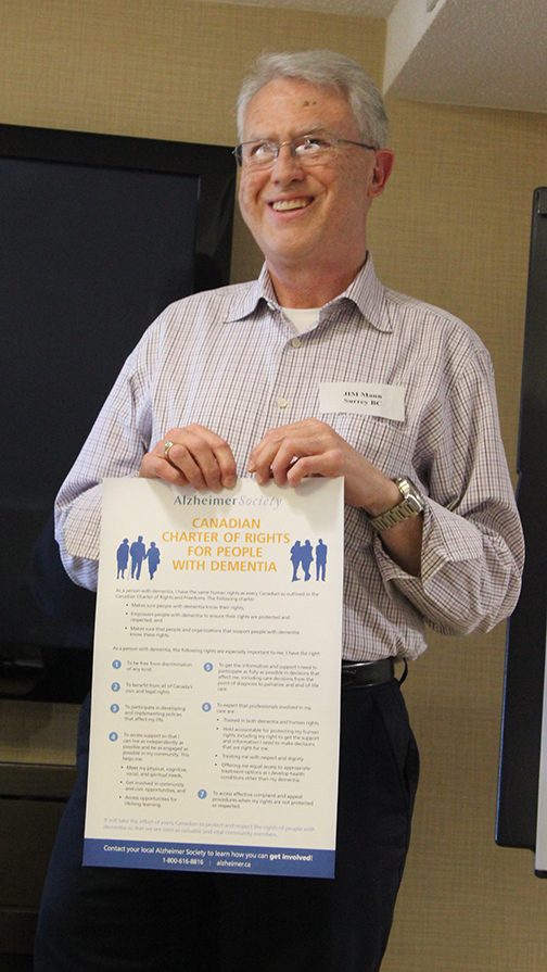 Jim Mann holding the Canadian Charter of Rights for People with Dementia.