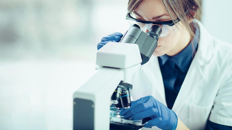 Female scientist investigating something using her microscope.