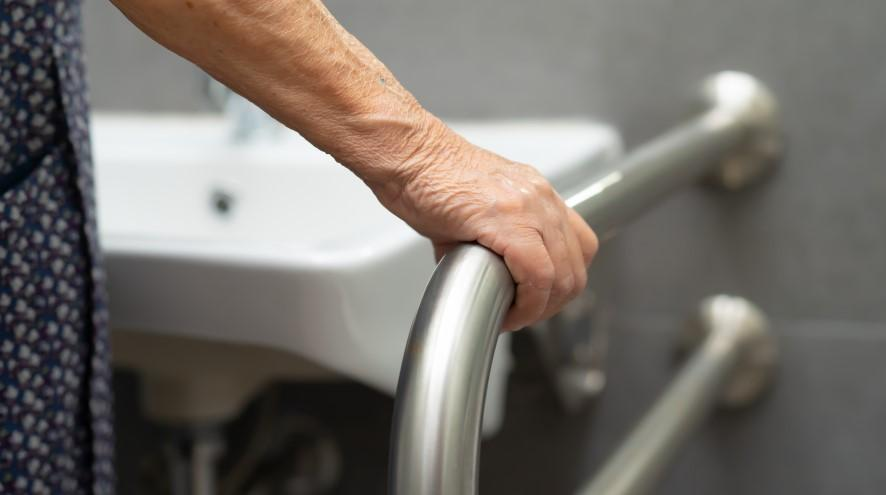 Senior holding the handrail in a bathroom.