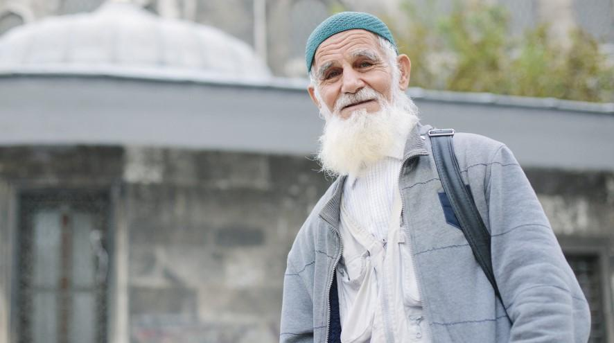 Senior man in front of mosque.