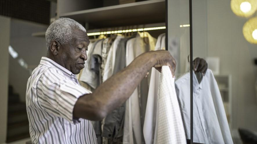 Senior man picking out a shirt to wear.