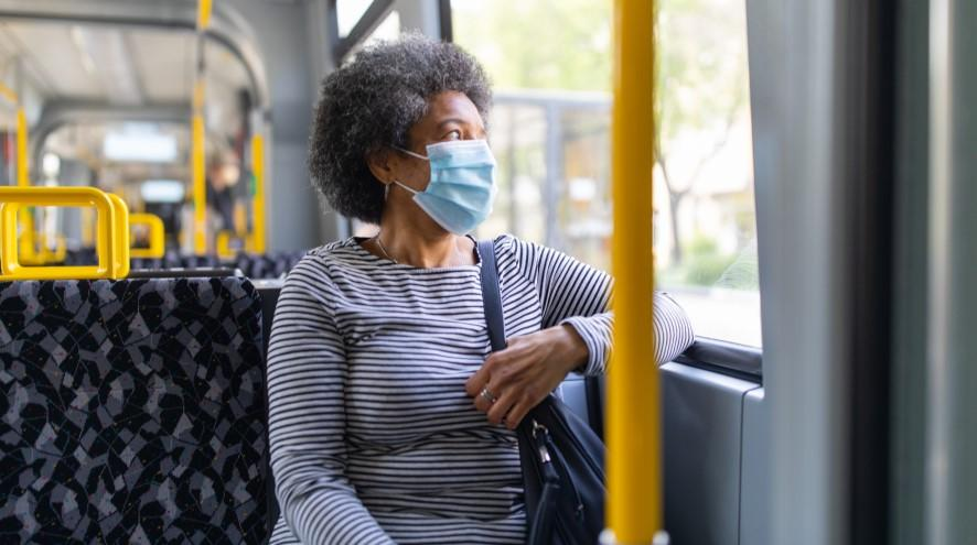 Senior woman on bus wearing mask.