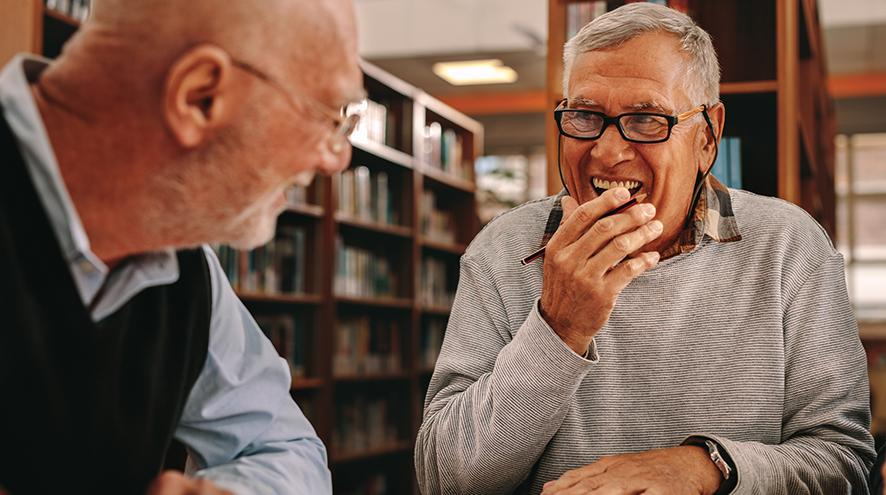 Two seniors in a library.