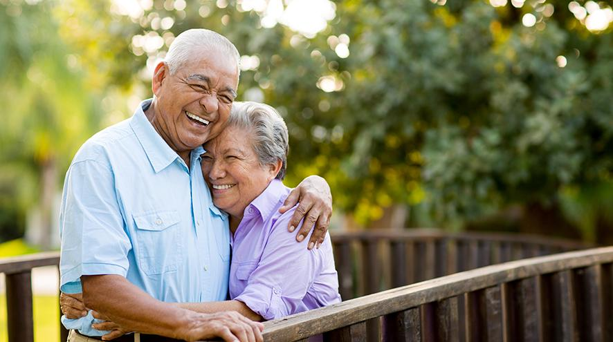 Senior couple laughing together on balcony.