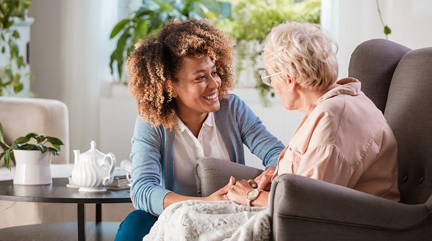 Friendly healthcare worker talking to a senior client.