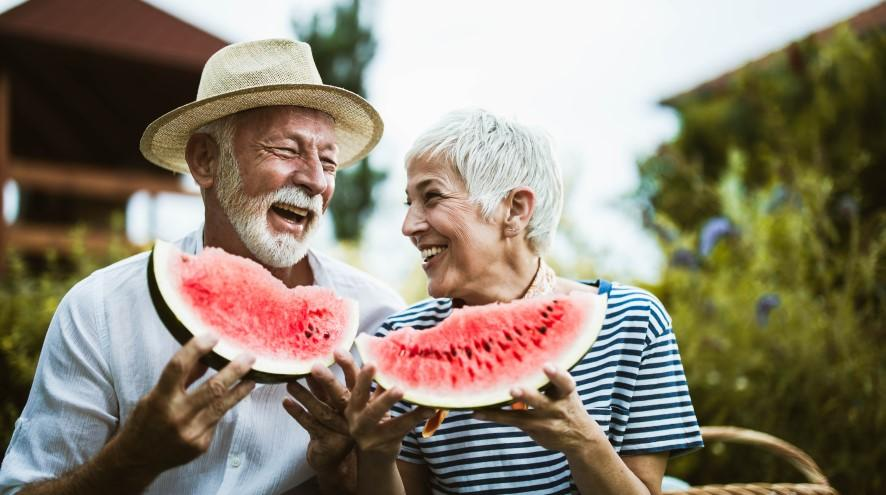 Senior couple eating a watermelon together.