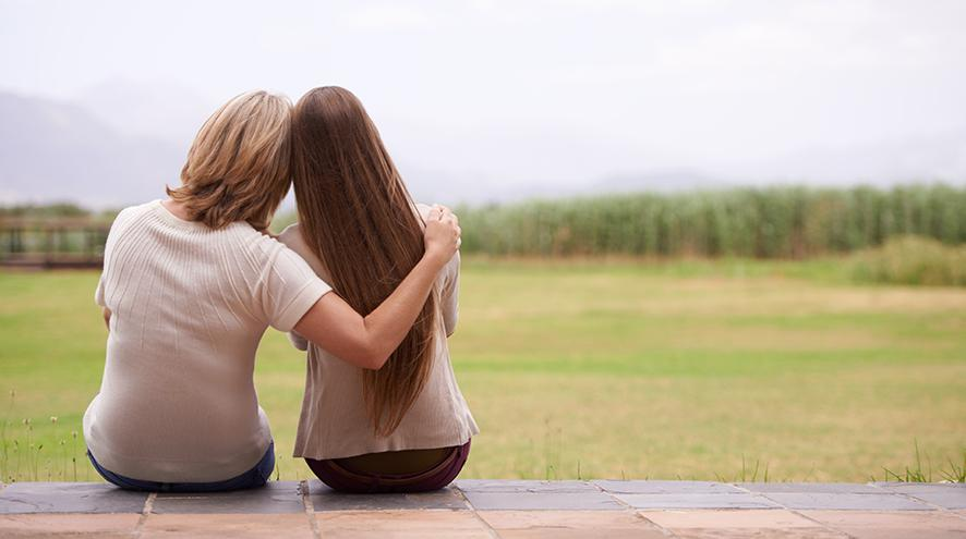 Mother and daughter looking at the forested horizon together.