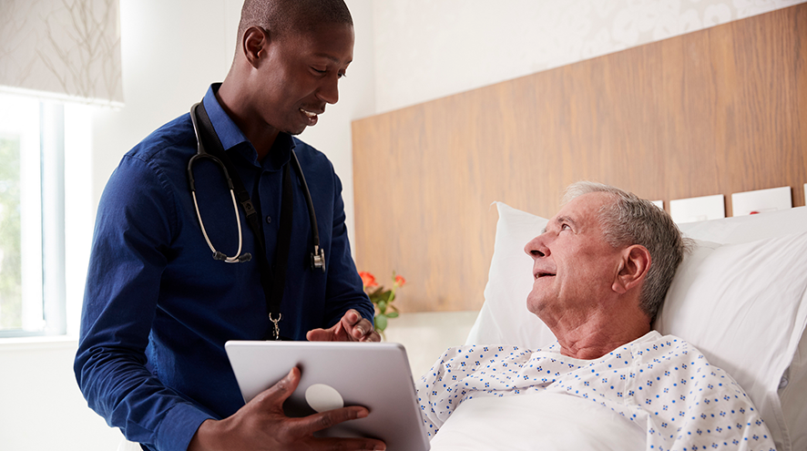 A doctor shows an older adult hospital patient something on a tablet.