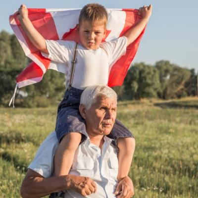 Young boy holding a Canadian flag and sitting on his grandfather's shoulders.