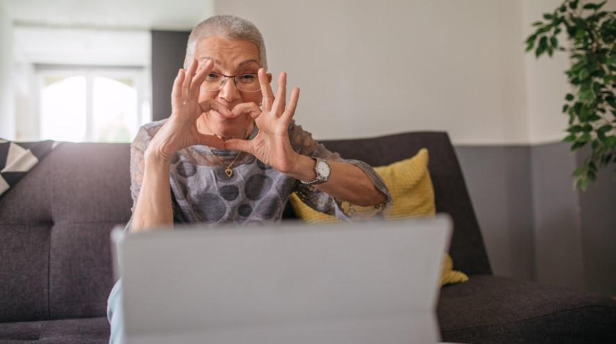 Smiling senior woman giving the heart symbol to a friend over a video call.