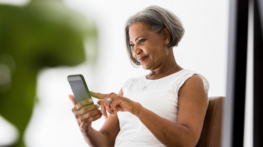 Female sitting down and using a cell phone.