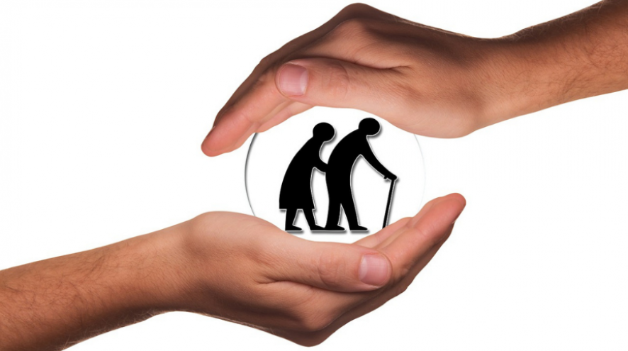 Image of hands holding the silhouette of an older couple in a glass ball.
