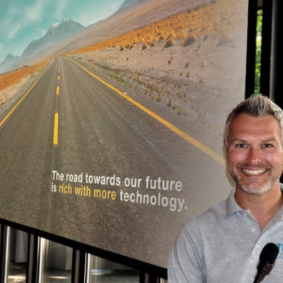 Image of Chris Bint, CEO and chief learning officer for Tech coaches, in front of a sign of the open road.