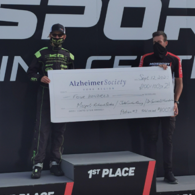 Jake Cowden holding a giant Alzheimer Society of York Region cheque after his recent go-kart win