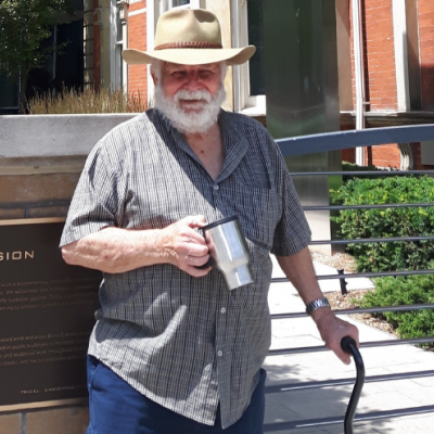 Picture of Bruce Howie in cowboy hat with coffee cup standing in front of a building holding onto a cane.