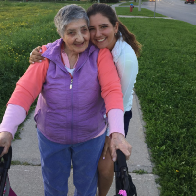 Gioulizar Smoian, who lives with dementia, standing with her walker and her granddaughter Selena Costabile hugging on a sidewalk